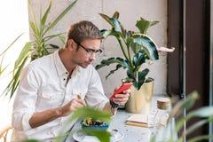 Εργατικός επιχειρηματίας που ελέγχει το ηλεκτρονικό ταχυδρομείο του στο τηλέφωνο που έχει το μεσημεριανό γεύμα στοκ φωτογραφία με δικαίωμα ελεύθερης χρήσης