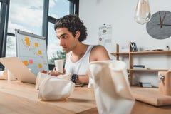 εργατικός επιχειρηματίας στο εσώρουχο με τη μίας χρήσης διαθέσιμη δακτυλογράφηση φλιτζανιών του καφέ στο lap-top στοκ φωτογραφία