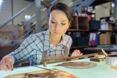 Εργατικός θηλυκός ξυλουργός που χρησιμοποιεί το λειαντικό έγγραφο στοκ εικόνα