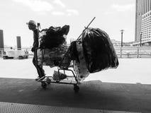 Εργατικός μπορέστε συλλέκτης με τις πλήρεις τσάντες των δοχείων σε αγορές γ Στοκ Εικόνα