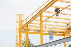 Εργατικό δυναμικό που χρωματίζει την κίτρινη δομή μετάλλων χρώματος στην κορυφή στεγών Στοκ Φωτογραφία