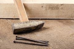 Εργαλεία Ένα σφυρί και καρφιά στο ξύλινο υπόβαθρο ready work Στοκ εικόνα με δικαίωμα ελεύθερης χρήσης