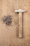 Εργαλεία Ένα σφυρί και καρφιά στο ξύλινο υπόβαθρο ready work Στοκ Εικόνα