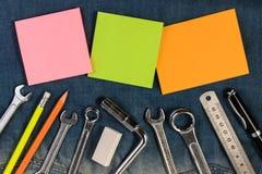 Εργαλεία γαλλικών κλειδιών στους εργαζομένους ενός τζιν με το κενό έγγραφο σημειώσεων για το κείμενο Στοκ Φωτογραφίες