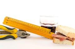 Εργαλεία εργασίας με ένα σάντουιτς και ένα ποτήρι του κόκκινου κρασιού στοκ φωτογραφία με δικαίωμα ελεύθερης χρήσης