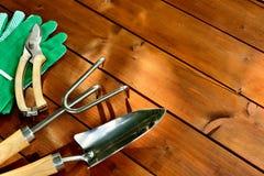Εργαλεία και αντικείμενα κηπουρικής κινηματογραφήσεων σε πρώτο πλάνο στο παλαιό ξύλινο υπόβαθρο με το copyspace Στοκ Εικόνα