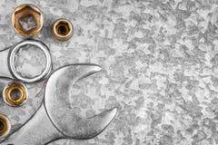 Εργαλεία και καρύδια γαλλικών κλειδιών σε ένα μεταλλικό υπόβαθρο στοκ φωτογραφία