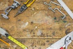Εργαλεία κατά μήκος των συνόρων της φορεμένης ξύλινης επιφάνειας πάγκων εργαστηρίων Στοκ εικόνες με δικαίωμα ελεύθερης χρήσης