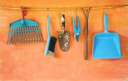 Εργαλεία κηπουρικής που κρεμούν σε έναν πορτοκαλή τοίχο Στοκ Εικόνες
