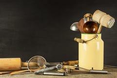 Εργαλεία κουζινών σε έναν ξύλινο πίνακα Cook& x27 εργαλεία του s Παραδοσιακός εξοπλισμός της αγροτικής κουζίνας Στοκ Εικόνες