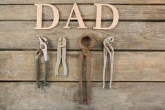 Εργαλεία χεριών που τακτοποιούνται από το κείμενο μπαμπάδων στον ξύλινο πίνακα Στοκ Εικόνα