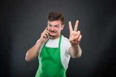 Εργοδότης υπεραγορών που μιλά στο τηλέφωνο που παρουσιάζει χειρονομία ειρήνης Στοκ φωτογραφία με δικαίωμα ελεύθερης χρήσης