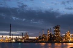 Εργοστάσιο εγκαταστάσεων καθαρισμού πετρελαίου στην ακτή νερού στο σούρουπο στοκ εικόνα με δικαίωμα ελεύθερης χρήσης