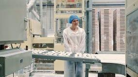 Εργοστάσιο καραμελών Ελεγκτής που ελέγχει το μεταφορέα με τις καραμέλες απόθεμα βίντεο