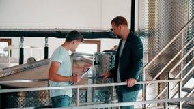Εργοστάσιο κρασιού ιδιοκτητών που μιλά με τον υπάλληλο στον εξοπλισμό παραγωγής υποβάθρου απόθεμα βίντεο