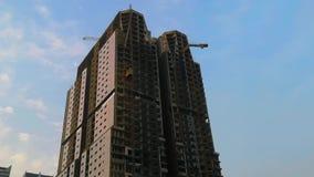 Εργοτάξιο οικοδομής, γερανός και μεγάλο κτήριο κάτω από την οικοδόμηση ενάντια στον ουρανό ηλιοβασιλέματος απόθεμα βίντεο