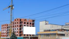 Εργοτάξιο οικοδομής ενός νέου υψηλού κτηρίου διαμερισμάτων με τους γερανούς πύργων ενάντια στο μπλε ουρανό Bikeboard στο υπόβαθρο Στοκ φωτογραφίες με δικαίωμα ελεύθερης χρήσης