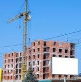 Εργοτάξιο οικοδομής ενός νέου υψηλού κτηρίου διαμερισμάτων με τους γερανούς πύργων ενάντια στο μπλε ουρανό Bikeboard στο υπόβαθρο Στοκ Εικόνα