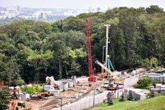 Εργοτάξιο οικοδομής με τους γερανούς και το φυσικό υπόβαθρο Στοκ εικόνα με δικαίωμα ελεύθερης χρήσης
