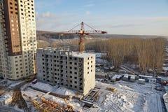 Εργοτάξιο οικοδομής με το γερανό και κάτω από το σπίτι διαμερισμάτων πολυκατοικίας κατασκευής Στοκ Φωτογραφία