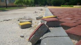 Εργοτάξιο οικοδομής, ο χρωματισμένος Stone οδικής επίστρωσης σε ένα πάρκο πόλεων, διαδικασία οικοδόμησης φιλμ μικρού μήκους