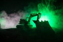 Εργοτάξιο οικοδομής σε μια οδό πόλεων Ένας κίτρινος digger εκσκαφέας που σταθμεύουν κατά τη διάρκεια της νύχτας σε ένα εργοτάξιο  Στοκ Εικόνα