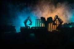 Εργοτάξιο οικοδομής σε μια οδό πόλεων Ένας κίτρινος digger εκσκαφέας που σταθμεύουν κατά τη διάρκεια της νύχτας σε ένα εργοτάξιο  Στοκ Φωτογραφίες