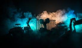 Εργοτάξιο οικοδομής σε μια οδό πόλεων Ένας κίτρινος digger εκσκαφέας που σταθμεύουν κατά τη διάρκεια της νύχτας σε ένα εργοτάξιο  Στοκ εικόνες με δικαίωμα ελεύθερης χρήσης
