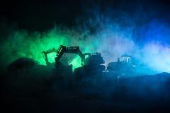 Εργοτάξιο οικοδομής σε μια οδό πόλεων Ένας κίτρινος digger εκσκαφέας που σταθμεύουν κατά τη διάρκεια της νύχτας σε ένα εργοτάξιο  Στοκ Φωτογραφία