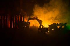 Εργοτάξιο οικοδομής σε μια οδό πόλεων Ένας κίτρινος digger εκσκαφέας που σταθμεύουν κατά τη διάρκεια της νύχτας σε ένα εργοτάξιο  Στοκ φωτογραφία με δικαίωμα ελεύθερης χρήσης
