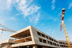 Εργοτάξιο οικοδομής με τους γερανούς πέρα από το μπλε ουρανό Στοκ Εικόνα