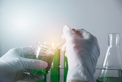 Ερευνητής με σωλήνες εργαστηριακής τους χημικούς δοκιμής γυαλιού με το υγρό στοκ φωτογραφία με δικαίωμα ελεύθερης χρήσης