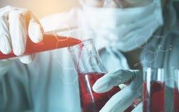 Ερευνητής με σωλήνες εργαστηριακής τους χημικούς δοκιμής γυαλιού με το υγρό στοκ φωτογραφία