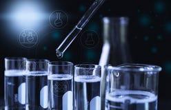 Ερευνητής με σωλήνες εργαστηριακής τους χημικούς δοκιμής γυαλιού με το υγρό για αναλυτικό, ιατρικός, φαρμακευτικός και τη επιστημ στοκ φωτογραφία