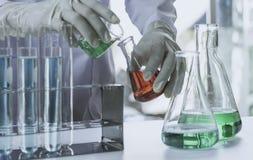 Ερευνητής με σωλήνες εργαστηριακής τους χημικούς δοκιμής γυαλιού με το υγρό για αναλυτικό, ιατρικός, φαρμακευτικός και τη επιστημ στοκ φωτογραφίες με δικαίωμα ελεύθερης χρήσης