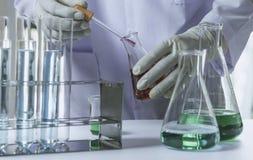 Ερευνητής με σωλήνες εργαστηριακής τους χημικούς δοκιμής γυαλιού με το υγρό για αναλυτικό, ιατρικός, φαρμακευτικός και τη επιστημ στοκ εικόνες