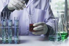 Ερευνητής με σωλήνες εργαστηριακής τους χημικούς δοκιμής γυαλιού με το υγρό για αναλυτικό, ιατρικός, φαρμακευτικός και τη επιστημ στοκ φωτογραφία με δικαίωμα ελεύθερης χρήσης