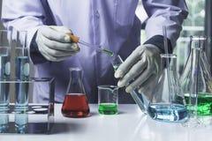Ερευνητής με σωλήνες εργαστηριακής τους χημικούς δοκιμής γυαλιού με το υγρό για αναλυτικό, ιατρικός, φαρμακευτικός και τη επιστημ στοκ εικόνα με δικαίωμα ελεύθερης χρήσης