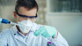Ερευνητής με το σωλήνα και dropper στο σύγχρονο εργαστήριο απόθεμα βίντεο