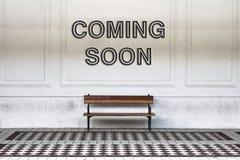 Ερχομός που γράφεται σύντομα σε έναν τοίχο επάνω από έναν ξύλινο πάγκο - ima έννοιας στοκ εικόνα με δικαίωμα ελεύθερης χρήσης