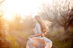 ερχόμενη άνοιξη Ευτυχής όμορφη νέα γυναίκα που τρέχει και που έχει τη διασκέδαση στο πάρκο ανθών Στοκ Φωτογραφίες