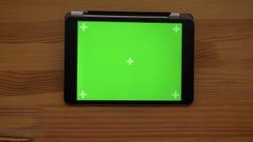 Ερχόμενη κοντινότερη κινηματογράφηση σε πρώτο πλάνο που πυροβολείται της οριζόντιας ταμπλέτας με την πράσινη οθόνη στο ξύλινο υπό απόθεμα βίντεο