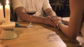 Ερωτευμένα χέρια εκμετάλλευσης ζεύγους στον πίνακα με τα κεριά και γυαλί κρασιού στη ρομαντική ημερομηνία στο εστιατόριο Εκμετάλλ φιλμ μικρού μήκους