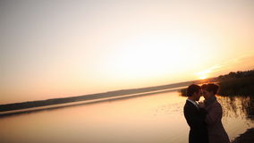 Ερωτευμένη πίσω ελαφριά σκιαγραφία ζεύγους στο πορτοκαλί ηλιοβασίλεμα λιμνών φιλμ μικρού μήκους