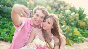 Ερωτευμένη παίρνοντας αυτοπροσωπογραφία ζευγών χαμόγελου νέα με το τηλέφωνο καμερών στην παραλία απόθεμα βίντεο