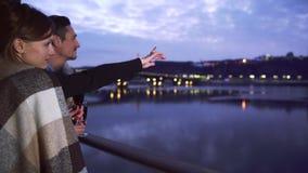 Ερωτευμένη στάση ζεύγους στο μπαλκόνι του ξενοδοχείου με τα γυαλιά κρασιού που απολαμβάνουν τη θέα της πόλης νύχτας Υπόλοιπο απόθεμα βίντεο