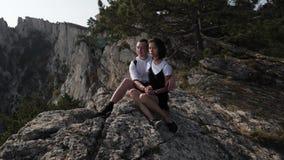 Ερωτευμένη συνεδρίαση ζεύγους στην άκρη ενός βουνού φιλμ μικρού μήκους
