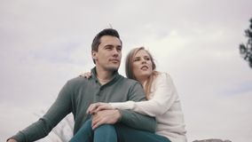Ερωτευμένη συνεδρίαση ζεύγους στη χλόη και αγκάλιασμα σε ένα πάρκο απόθεμα βίντεο