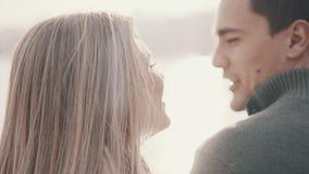 Ερωτευμένη συνεδρίαση ζεύγους στη χλόη και αγκάλιασμα σε ένα πάρκο φιλμ μικρού μήκους