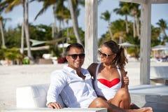 Ερωτευμένη χαλάρωση ζευγών μήνα του μέλιτος ρομαντική στην παραλία πολυτέλειας Στοκ εικόνες με δικαίωμα ελεύθερης χρήσης